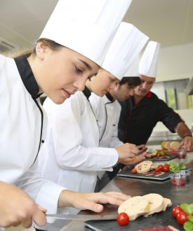 Group of cooks working with chef in kitchen